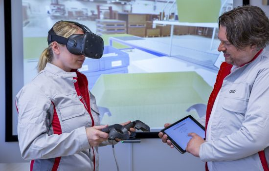 Together with atrainer, an Audi Packing Logistics employee practices the proper techniques for packing brake discs and other large parts for shipping overseas. Thanks toapair of virtual reality glasses, she can train in arealistic and true-to-life simulation of her work station in Hall L of the Ingolstadt Logistics Center.